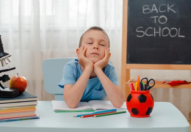 Der lügenschreibtisch des schuljungen, der zu hause klassenzimmer sitzt, füllte mit den büchern, die das materielle schulkind ausbilden, das faul gelangweilt schläft