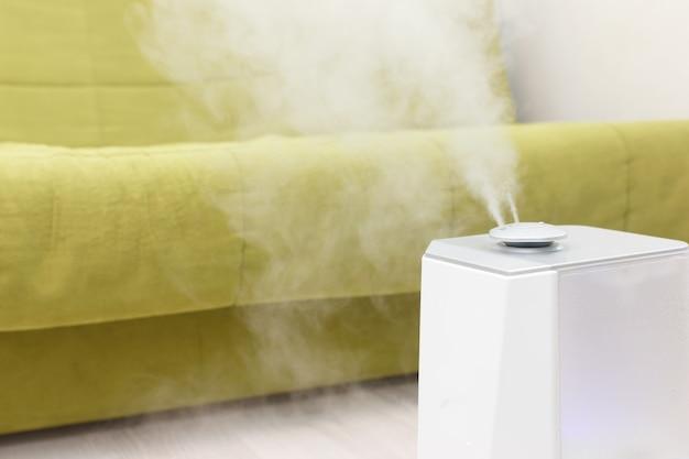 Der luftbefeuchter arbeitet im raum mit grünem sofa