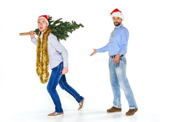 Der lustige junge mann in der weihnachtsmannmütze, die weihnachtsbaum ausführt