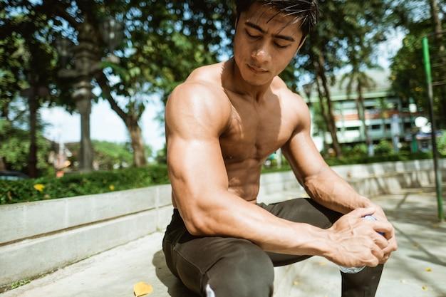 Der macho-mann ohne hemd sitzt und hält eine trinkflasche, während er im freien im park trainiert