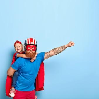Der mächtige vater gibt dem kind ein huckepack, zeigt mut, macht eine fliegende geste, trägt einen helm und eine rote maske