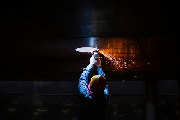 Der männliche arbeiter, der den dach-overhead-metallbogen schneidet, ist teil des maschinentankdüsenbogenbaus erdöl- und gaslagertank in beengten räumen.