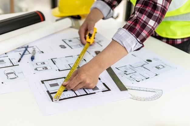 Der männliche architekt vermisst die hausentwürfe mit einem maßband, er überprüft die von ihm entworfenen hauspläne, bevor er sie an die kunden schickt, er entwirft das haus und die inneneinrichtung.