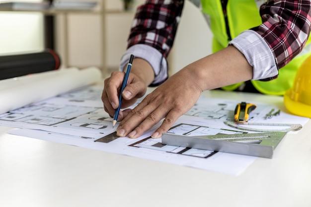 Der männliche architekt zeichnet auf den hausplänen, er prüft die von ihm entworfenen hauspläne vor dem versand an die kunden, er entwirft das haus und die inneneinrichtung. ideen für die wohngestaltung.