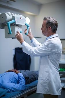 Der männliche arzt richtet das gerät so ein, dass es den patienten röntgt