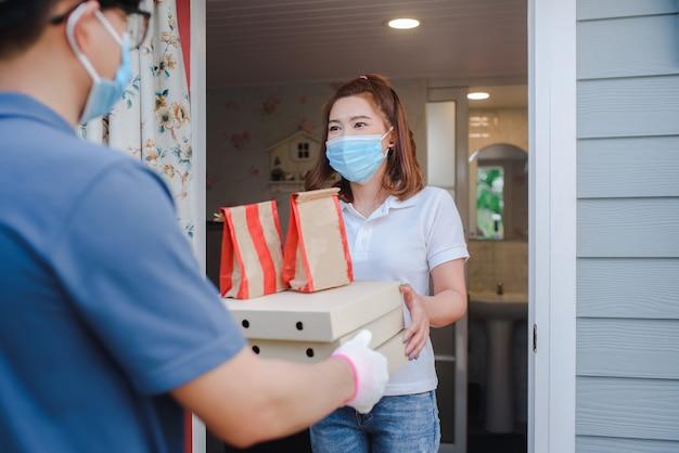 Der männliche asiatische versender lieferte die ware mit einer papierschachtel in der lebensmittellieferuniform an eine schöne kundin vor dem haus. konzept des express-lebensmittellieferservices