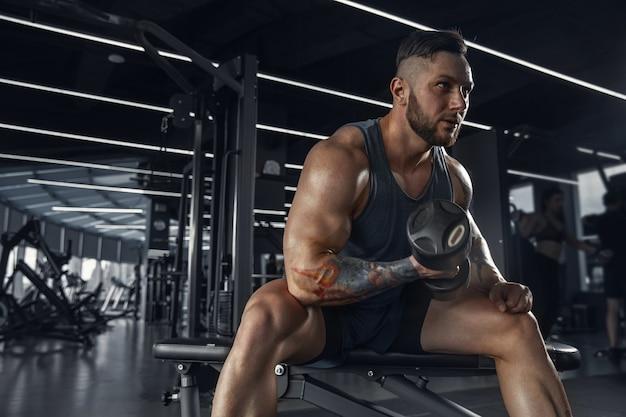 Der männliche athlet trainiert hart im fitnessstudio