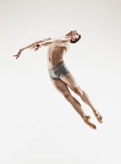 Der männliche athletische balletttänzer, der den tanz lokalisiert auf weißem hintergrund durchführt. studioaufnahme. ballett-konzept. fitter junger mann. kaukasisches modell