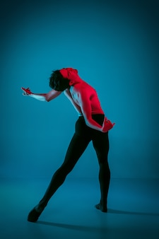 Der männliche athletische balletttänzer, der tanz auf lebendigem blauem hintergrund durchführt. studioaufnahme. modernes ballett, zeitgenössisches konzept. fitter junger mann. kaukasisches modell