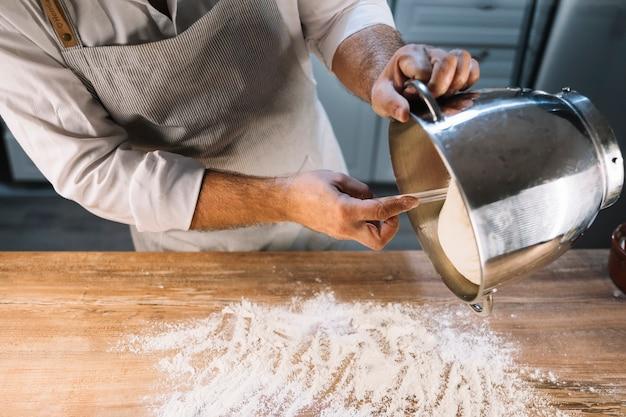Der männliche bäcker, der knetenden teig vom behälter auf holztisch gießt, wischte mit mehl ab