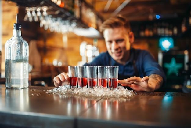Der männliche barkeeper bereitet vier getränke in gläsern zu