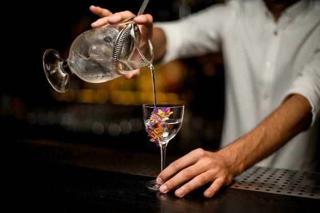 Der männliche barmixer, der ein cocktail vom messbecher mit einem sieb zu einer blume gießt, verzierte glas
