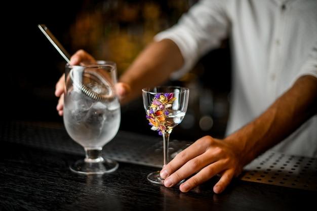 Der männliche barmixer, der eine messende schale des cocktails mit einem sieb und einer blume hält, verzierte glas