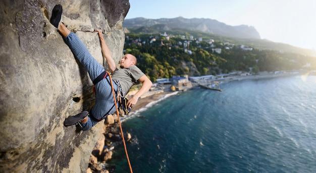 Der männliche bergsteiger macht es schwierig, auf die überhängende klippe zu steigen