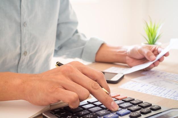 Der männliche butler sitzt, drückt auf den taschenrechner, hält mehrere rechnungen, berechnet einnahmen und ausgaben. ist ein investitionsplan.