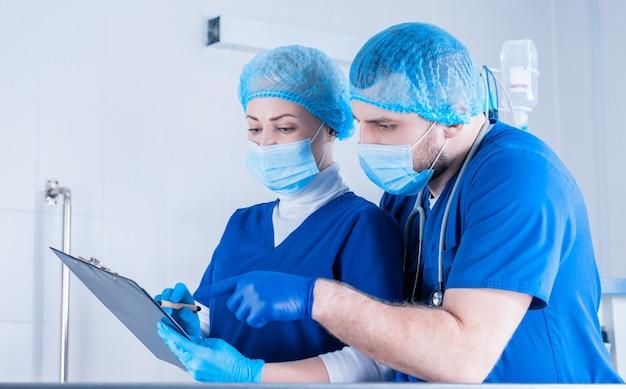 Der männliche chirurg erklärt der anästhesistin. und sie macht sich notizen auf dem tablett