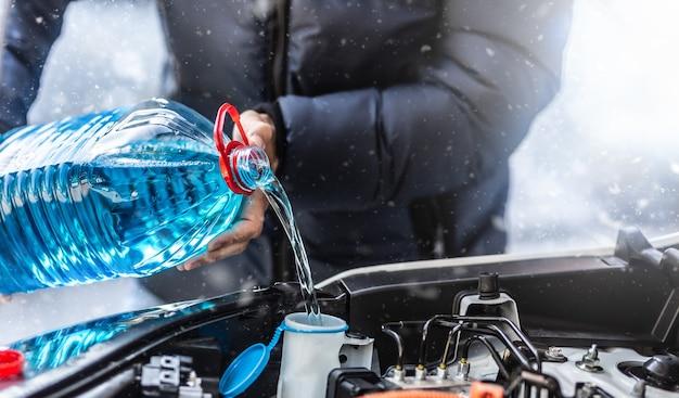 Der männliche fahrer gießt frostschutzmittel in den tank, um bei einem schneesturm die windschutzscheibe zu besprühen.