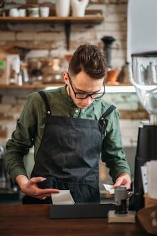 Der männliche kellner bereitet den check-in im kaffeehaus vor.