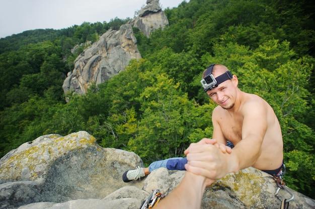 Der männliche kletterer greift nach einer helfenden hand seines partners