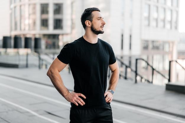 Der männliche läufer hielt beim joggen an, um den schönen morgenblick auf die stadt zu bewundern. mann in schwarzer sportkleidung, der seine hände an der taille hält und wegschaut. urbanes sportkonzept. morgentraining.