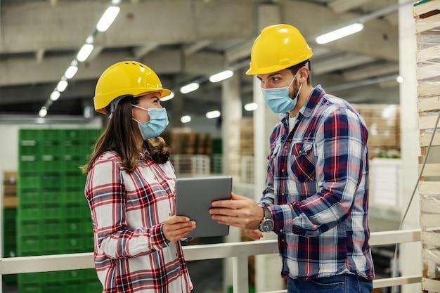 Der männliche lagerleiter zeigt informationen über die digitalen tablet-mitarbeiter im lager und sie haben einen lustigen moment. sie tragen einen schutzhelm und eine gesichtsmaske, sicherheit am arbeitsplatz. corona