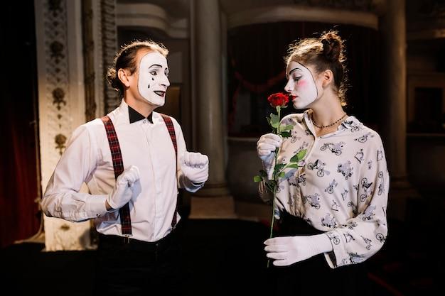 Der männliche pantomimekünstler, der den weiblichen pantomimen betrachtet, der rote rose riecht