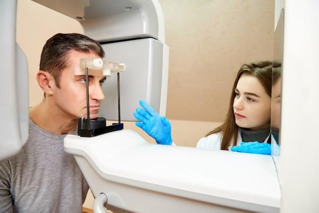 Der männliche patient befindet sich im scanner, und der girldoctor befindet sich in der nähe des bedienfelds.