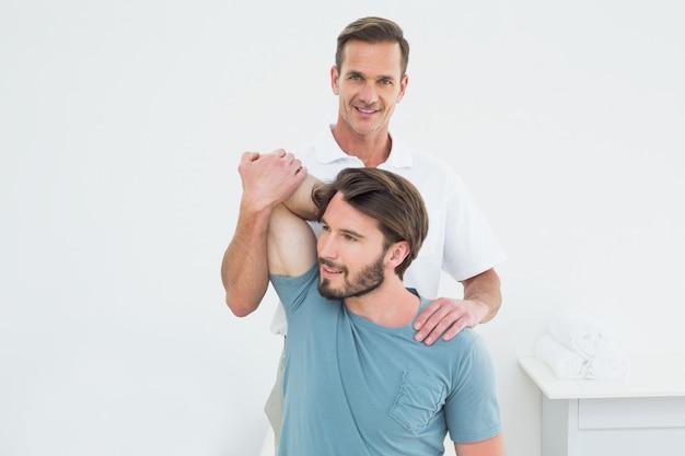 Der männliche physiotherapeut, der ein junges ausdehnt, bemannt arm