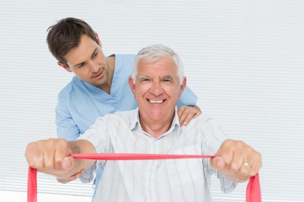 Der männliche physiotherapeut, der senior massiert, bemannt zurück