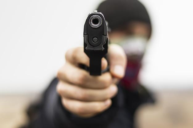 Der männliche verbrecher, der mit einer handfeuerwaffe angreift, begeht ein verbrechen