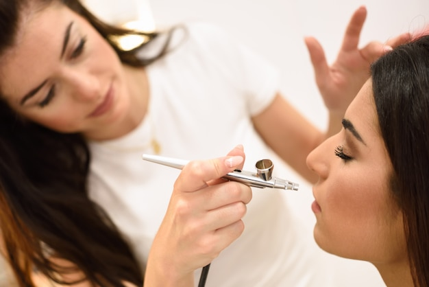 Der make-upkünstler, der den aerograph verwendet, der eine spritzpistole bildet, bilden