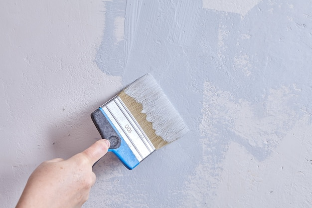 Der maler malt während der renovierung die wand mit hilfe von pinsel und farbe.