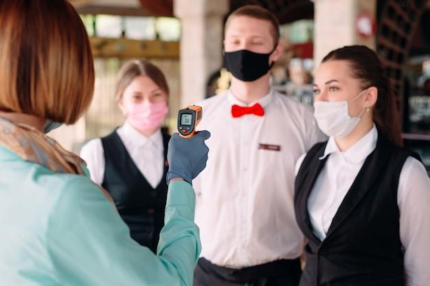 Der manager eines restaurants oder hotels überprüft die körpertemperatur des personals mit einem wärmebildgerät.