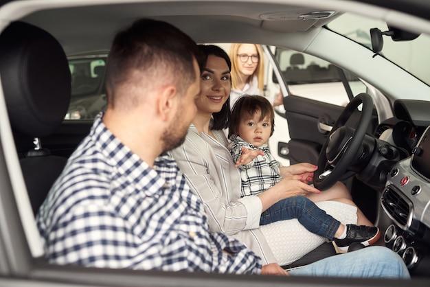 Der manager hilft der jungen familie, das bequemste auto für die stadt auszuwählen.