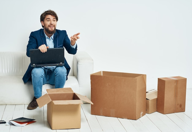 Der manager sitzt in der nähe des sofas und packt dinge, die an einen neuen arbeitsplatz umziehen