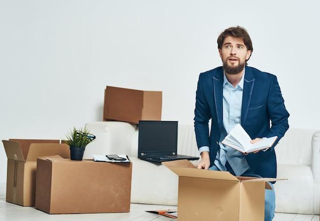 Der manager sitzt neben dem sofa, packt sachen und zieht an einen neuen arbeitsplatz