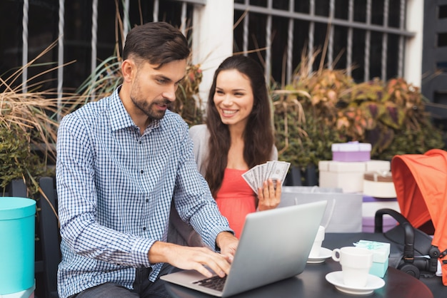 Der mann arbeitet an einem laptop, während frau lächeln.