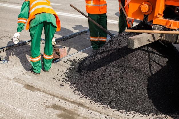 Der mann arbeitet asphalt gießt teer für die straßenreparatur