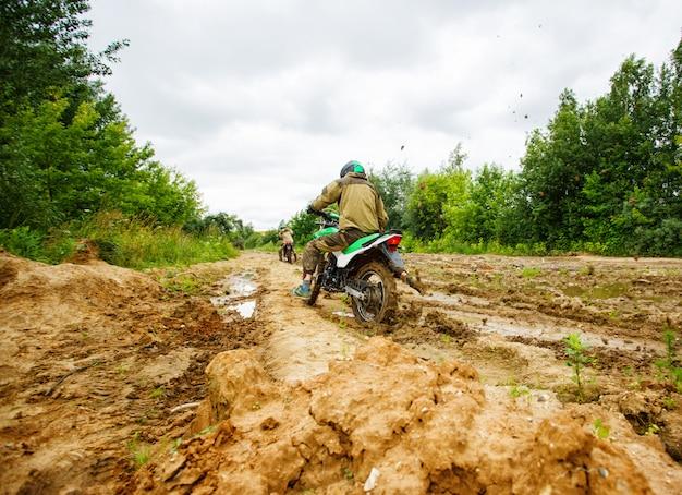 Der mann auf einem motorrad fährt durch den schlamm