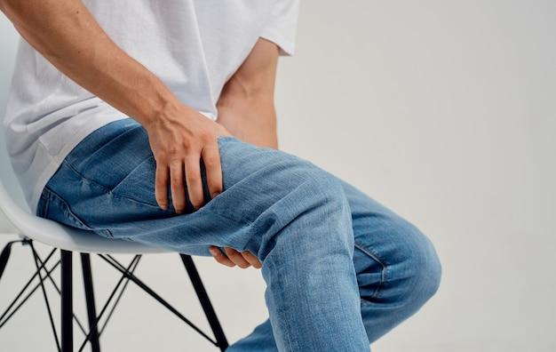 Der mann berührt sein bein mit den händen auf einem leichten hintergrundknieschmerzen