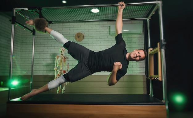 Der mann beschäftigt sich mit pilates. fitness und sport