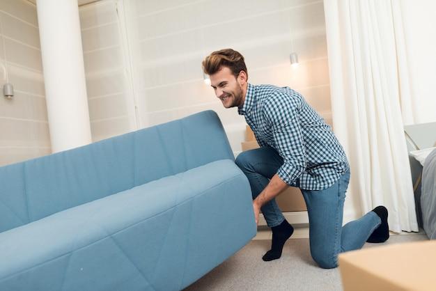 Der mann bewegt das sofa, während er in ein neues zuhause zieht.