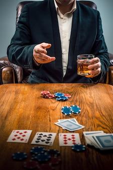 Der mann, chips für glücksspiele, getränke und spielkarten