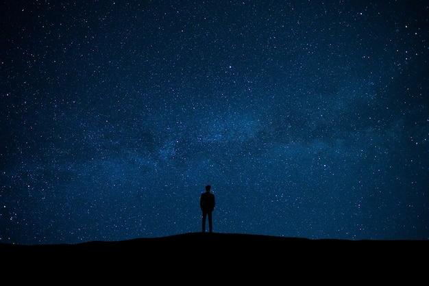 Der mann, der auf dem sternenhimmelhintergrund steht