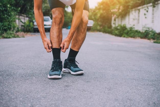 Der mann, der auf der straße läuft, läuft für übung, lässt sport und nahaufnahme am laufschuh laufen