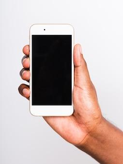 Der mann, der den leeren bildschirm des weißen mobilen smartphones des modells auf der hand hält