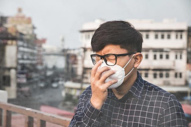 Der mann, der die atemschutzmaske gegen luftverschmutzung und staubpartikel trägt, überschreitet die sicherheitsgrenzen. gesundheits-, umwelt-, ökologiekonzept.