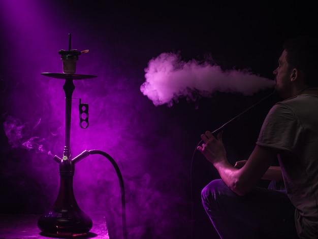 Der mann, der die klassische shisha raucht. schöne farbige licht- und rauchstrahlen. das konzept des shisha-rauchens.