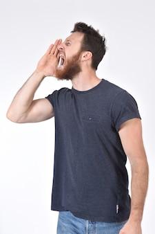 Der mann, der eine hand in mund einsetzt und schreit auf weiß