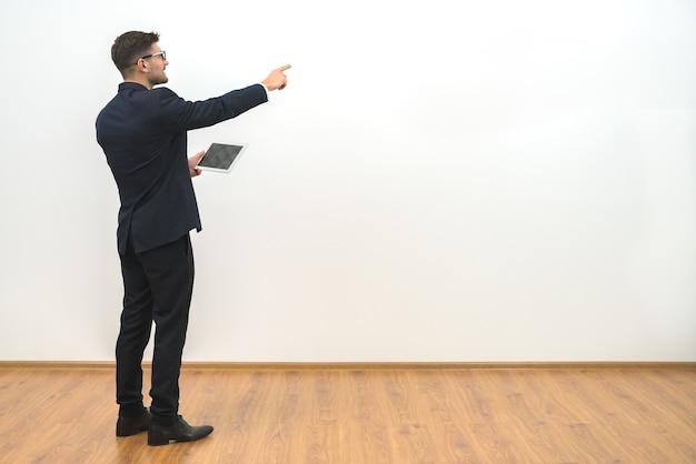 Der mann, der eine tablette hält und auf den weißen wandhintergrund gestikuliert